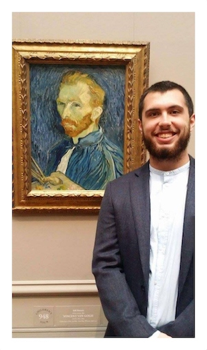 Travis Simmons stands smiling next to a portrait of Vincent van Gogh.