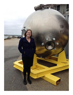 Bonnie Hurwitz stands outdoors next to the main chamber of the Alvin submersible, a large, round, silver pod.