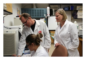 Three researchers gathered in a lab wearing white coats examine something together.