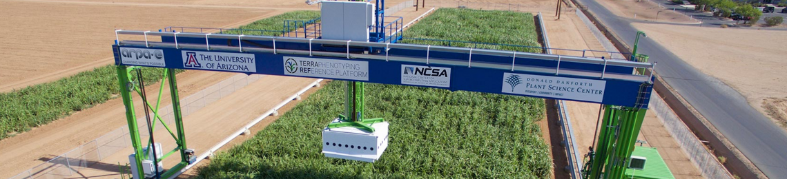 The 30-ton Field Scanalyzer, the world's largest agricultural robot, bridges a row of green crops as it scans them.